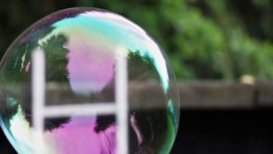 A close-up shot of a soap bubble with a garden in the background.