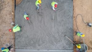 Construction workers pour concrete while on a work site.