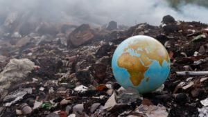 An intact globe is surrounded by a pile of garbage and burning waste. to represent esg investing