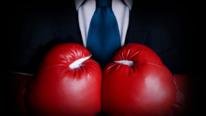Image of a businessman wearing red boxing gloves