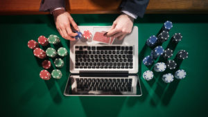 Image of a laptop surrounded by gambling paraphernalia.