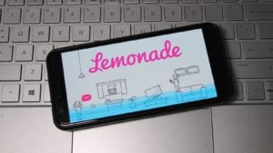 Lemonade logo displayed on smartphone laying on top of computer keyboard.