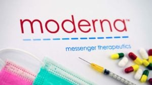 The Moderna (MRNA) logo surrounded by syringes, pills and disposable face masks.