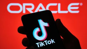 The TikTok logo is displayed on a smartphone in front of the Oracle (ORCL) sign.
