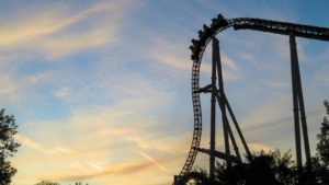 Sillhouette of a cart at the top of the hill on a roller coaster at sunset