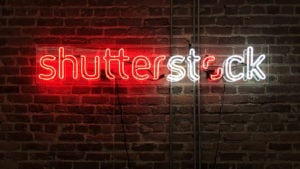 Neon sign of the Shutterstock logo glowing against an exposed brick wall in the San Francisco office of Shutterstock, Inc. (NYSE: SSTK).