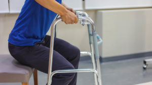 A man using a walker, about to stand from a chair.