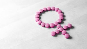 Pink pills form the shape of the Venus symbol on a light wooden background.