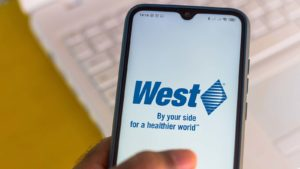 The West Pharmaceutical Services (WST) logo is displayed on a smartphone screen.