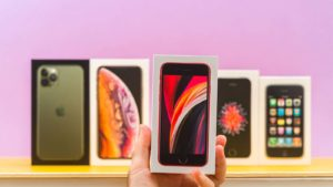 A close-up shot of different Apple (AAPL) iPhones in front of a purple background.