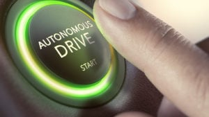 "A finger hovering over an ""autonomous drive"" button."