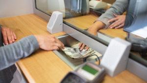 bank customer sliding money to teller at bank desk