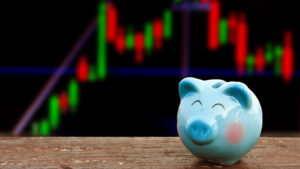 Smiling piggy bank against stock chart background. Represents cheap stocks and undervalued stocks.