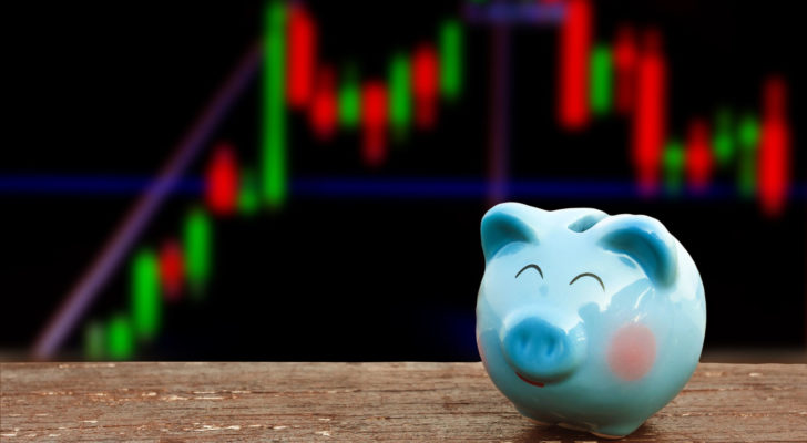 Smiling piggy bank against stock chart background. Represents cheap stocks and stocks selling at a discount
