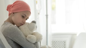 Image of a child cancer patient holding a stuffed bear.
