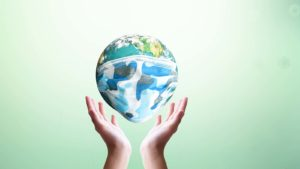 A digital image of hands holding up the planet Earth, which is wearing a face mask.