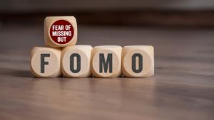 "Wooden blocks spell out ""FOMO"" and ""Fear of Missing Out."""