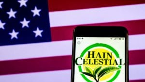 The logo for Hain Celestial (HAIN) displayed on a smartphone screen in front of an American flag.