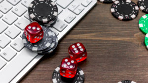 poker chips and dice on top of a keyboard representing gambling stocks