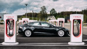 A black Tesla (TSLA) Model S is parked between rows of charging stations.