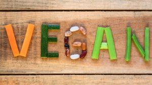 """Vegan"" spelled in vegetables against wooden backdrop."