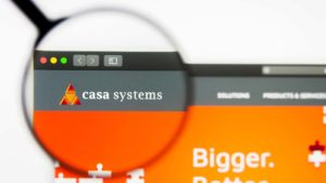 A magnifying glass zooms in on the website for Casa Systems (CASA).
