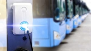 A close-up shot of an electric vehicle charging station with a row of electric buses in the background.