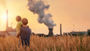 A father holds his son in a wheat field as they look at the smoke coming from a chemical plant's smokestack.