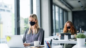 two women working on laptops in office space with black PPE face masks on