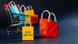 Shopping bags and an 11.11 sign are arranged around a miniature shopping cart.