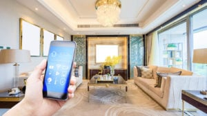 A hand holds a smart phone up with a fancy living room behind it.