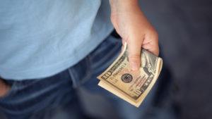 hand holding folded ten dollar bill