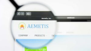 A magnifying glass zooms in on the website for Aemetis (AMTX).