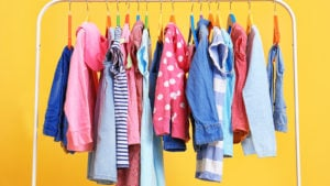 colorful clothes on a white rack with a bright yellow background