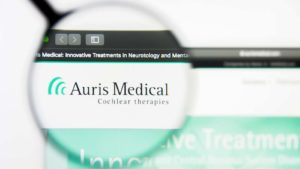 A magnifying glass zooms in on the website for Auris Medical Holdings (EARS).