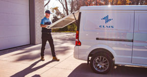Delivery man closing back door of ELMS EV van