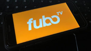 A picture of a FuboTV logo on a smart phone against a computer keyboard.