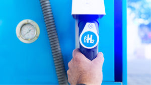 Man hold a fuel dispenser with hydrogen on gas station. h2 combustion engine for emission free eco friendly transport.