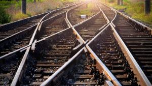A photo of train tracks leading toward a sunset.