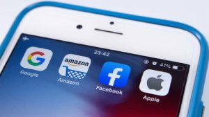 A smartphone screen displays apps for Facebook (FB), Apple (AAPL) and Amazon (AMZN)
