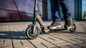 Man's legs riding a scooter over tiled sidewalk