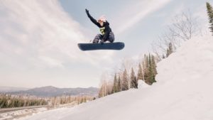 Image of a female snowboarding hitting a jump