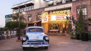 A shot of a historic police car in front of a Landry's seafood restaurant in Texas.
