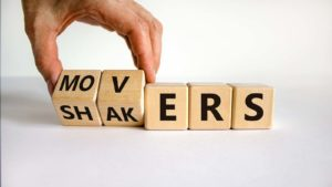 "A close-up shot of wooden blocks that spell out ""Movers"" and ""Shakers"""