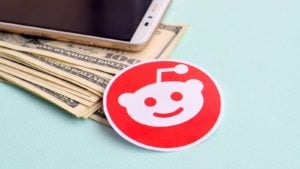 A Reddit sticker rests next to an iPhone and a pile of cash.