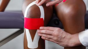 Image of a doctor applying kinesiology tape to patient's knee