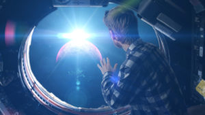 Person looking through space capsule's cabin window into space.