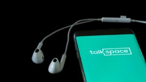 The Talkspace logo is displayed on a smartphone screen.