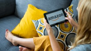 "Woman sitting on couch using tablet with ""Amazon"" on display."