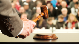Image of a hand holding a wooden hammer at an auction.